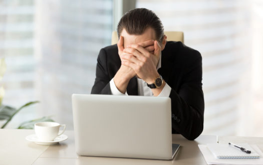 Terrified businessman covering face with hands in front of laptop.