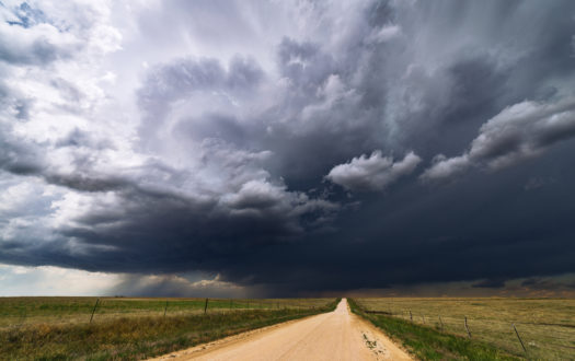 Stormy sky over a dirt road and field.