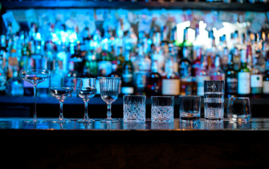 Several glasses of different forms stand on bar counter. Blue light on shelves with bottles of alcohol in background.